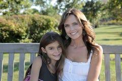 Madre e hija en banco de parque Fotos de archivo libres de regalías