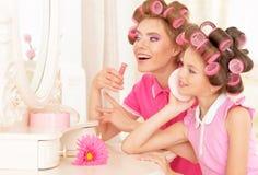 Madre e hija en bigudíes de pelo Foto de archivo libre de regalías