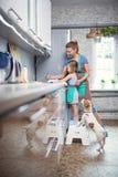 Madre e hija en casa en los platos que se lavan de la cocina foto de archivo