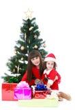 Madre e hija en el árbol de navidad Imágenes de archivo libres de regalías