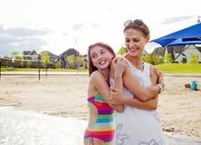 Madre e hija en el abarcamiento de la playa Imágenes de archivo libres de regalías