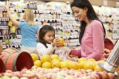 Madre e hija en el contador de la fruta en supermercado imágenes de archivo libres de regalías