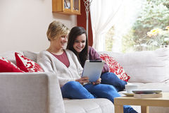Madre e hija en el ordenador de la tableta Fotografía de archivo