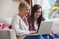 Madre e hija en el ordenador portátil Imagen de archivo libre de regalías