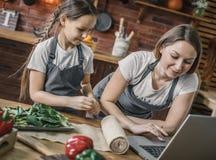 Madre e hija en el ordenador portátil en cocina Fotografía de archivo