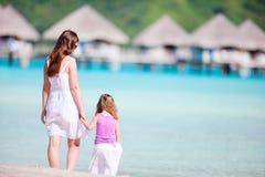 Madre e hija en la playa del centro turístico Foto de archivo libre de regalías