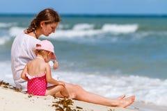 Madre e hija en la playa tropical Fotos de archivo