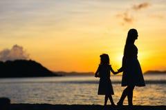 Madre e hija en la puesta del sol Fotografía de archivo