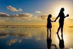 Madre e hija en la puesta del sol Imagenes de archivo
