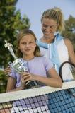 Madre e hija en la red del tenis con el retrato del trofeo Foto de archivo