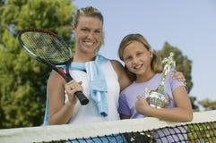 Madre e hija en la red del tenis con la opinión de ángulo bajo del retrato del trofeo Fotos de archivo
