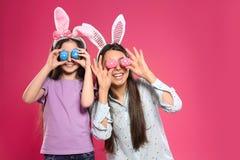 Madre e hija en las vendas de los o?dos del conejito que sostienen los huevos de Pascua cerca de ojos en color imagen de archivo libre de regalías