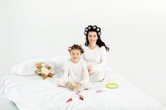 Madre e hija en los bigudíes y los pijamas que se sientan en cama y que sonríen en la cámara Imagen de archivo libre de regalías