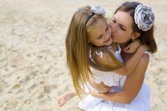 Madre e hija en los sundresses blancos en la playa Foto de archivo libre de regalías