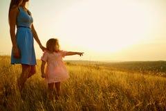 Madre e hija en naturaleza en la puesta del sol Imagen de archivo
