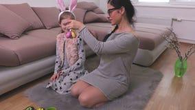 Madre e hija en piso con los huevos de Pascua decorativos