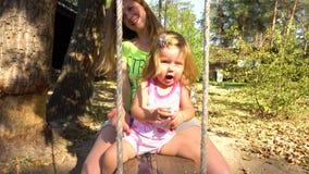 Madre e hija en tirón-aleta de madera debajo del árbol almacen de video