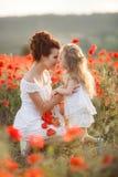 Madre e hija en un campo de amapolas florecientes foto de archivo libre de regalías