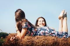 Madre e hija en un campo del otoño con la pila del heno Foto de archivo