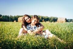 Madre e hija en un campo del otoño con la pila del heno Fotos de archivo