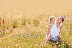 Madre e hija en un prado del verano Foto de archivo