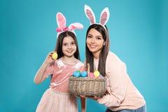 Madre e hija en vendas de los o?dos del conejito con la cesta de huevos de Pascua en color imagen de archivo libre de regalías