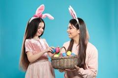 Madre e hija en vendas de los o?dos del conejito con la cesta de huevos de Pascua imagen de archivo