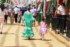 Madre e hija en vestido tradicional que caminan junto a Casetas en la Sevilla favorablemente Imagen de archivo libre de regalías