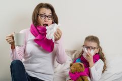 Madre e hija enfermas Una mujer con mocos, ella estornuda, usando un pañuelo, té caliente de consumición, medicina imagen de archivo