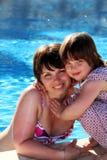 Madre e hija felices al lado de una piscina Imagen de archivo