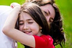 Madre e hija felices con el abarcamiento, retrato ascendente cercano Foto de archivo