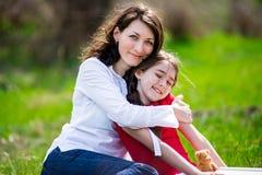 Madre e hija felices con el abarcamiento, retrato ascendente cercano Foto de archivo libre de regalías