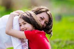 Madre e hija felices con el abarcamiento, retrato ascendente cercano Fotos de archivo libres de regalías