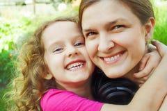 Madre e hija felices con el abarcamiento, retrato ascendente cercano ins Imagen de archivo libre de regalías