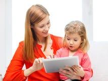 Madre e hija felices con el ordenador de la PC de la tableta Imagenes de archivo