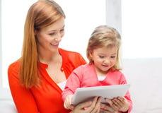 Madre e hija felices con el ordenador de la PC de la tableta Fotografía de archivo