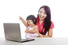 Madre e hija felices con la computadora portátil Fotos de archivo