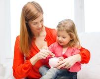 Madre e hija felices con la pequeña hucha Imágenes de archivo libres de regalías