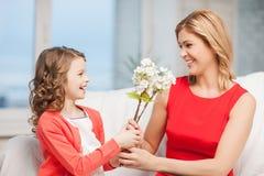 Madre e hija felices con las flores Imágenes de archivo libres de regalías