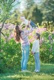 Madre e hija felices con las manzanas verdes en el jardín de lilas florecientes fotografía de archivo