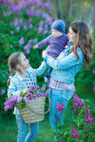 Madre e hija felices con las manzanas verdes en el jardín de lilas florecientes Imagen de archivo