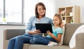 Madre e hija felices con PC de la tableta en casa foto de archivo libre de regalías