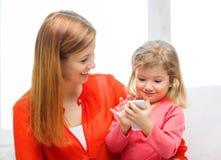 Madre e hija felices con smartphone en casa Foto de archivo libre de regalías