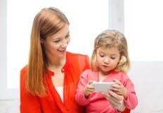 Madre e hija felices con smartphone en casa Imágenes de archivo libres de regalías