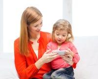 Madre e hija felices con smartphone en casa Imagen de archivo