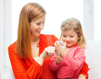 Madre e hija felices con smartphone en casa Fotos de archivo libres de regalías