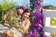 Madre e hija felices debajo del arco para el ceremon de la boda imagen de archivo
