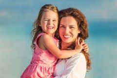 Madre e hija felices en la costa de mar Fotografía de archivo