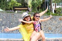 Madre e hija felices en la piscina con los brazos abiertos que gozan del th Fotografía de archivo