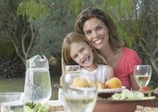 Madre e hija felices en la tabla del jardín Fotos de archivo